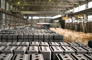 Wide angle background image of concrete blocks in warehouse of graphite plant, copy space